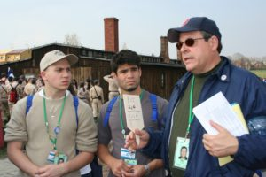 Image of Irv Kempner with two motl boy marchers discussing the crematoria of Majdanek used to dispose of the corpses.