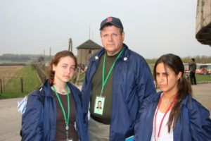 Image of Irv Kempner with two MOTL teenager girl marchers witness the Nazi guard towers and electrified fences of Majdanek death camp near Lublin.