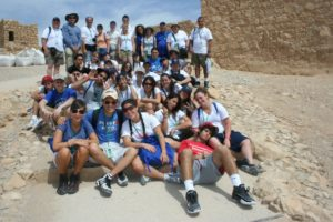 Image of March of the Living teenagers rest on top of Masada