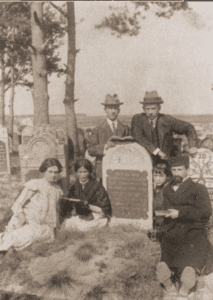 Image of Family gathered at a tombstone in the Wloszczowa