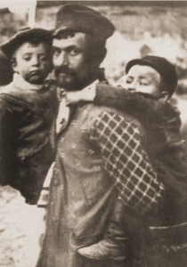 Image of Yitskhok Erlich, the belfer (helper of the melamed), carries youngsters to kheyder in Staszow.