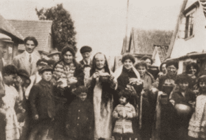 """Image of Housewives in Bialystok carry """"tsholnt"""", a dish of meat, potatoes, and beans, to the baker's oven on Friday afternoon."""