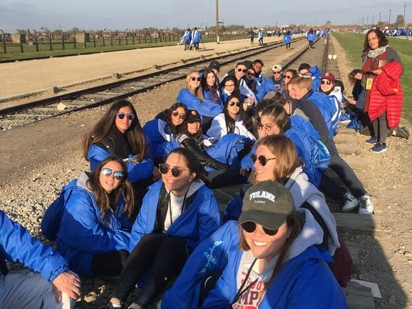 Image of MOTL teens sit on tracks to Auschwitz that carried millions to their deaths.
