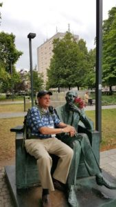 Image of Warsaw outside Polin Museum Irv sitting with statue tribute to Jan Karski, underground courier for the Polish government-in-exile, informed the West in the fall of 1942 about Nazi atrocities against Jews taking place in Poland.