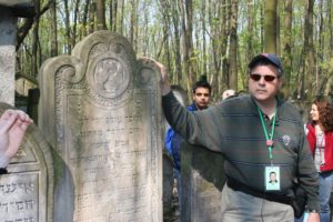 Image of Irv at Warsaw Cemetery headstones of his great grandparents.